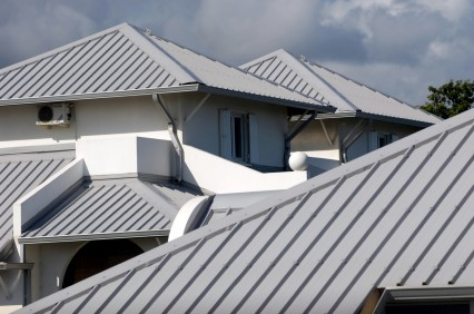 Series of grey gabled raised seam metal roofs on white houses
