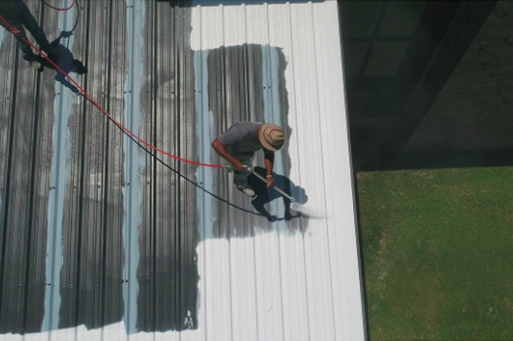 Man spray applies GAICO coating to flat roof on a sunny day.